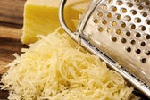 Grated Cheese and Grater on Board — Stock Photo
