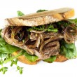 Steak Sandwich with Caramelized Onions and Herbs Isolated - Stock Photo