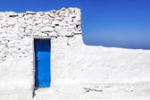 Mykonos Blue door in Whitewashed Wall — Stock Photo