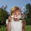 Girl play in bubbles — Stock Photo