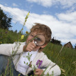 Boy with magnifying glass outdoors - Stok fotoğraf
