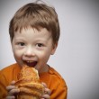 Happy boy with croissant — Stock Photo #17137411