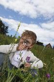 Boy with magnifying glass outdoors — Stock Photo
