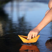 Paper ship in children hand — Stock Photo