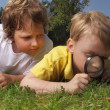 Two boys with magnifying glass outdoors — Stock Photo