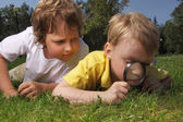 Two boys with magnifying glass outdoors — Stock fotografie