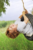 Happy boy on swing outdoors — Stock Photo