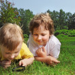 Two boys with magnifying glass outdoors — Stock Photo #23625017