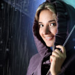 Woman under an umbrella in the rain — Stock Photo