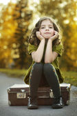 Resentful girl on suitcase — Stock Photo