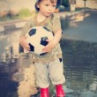 Happy boy with Ball in the spring puddle — Stockfoto