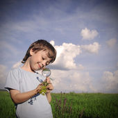 Child with magnifying glass — Stock Photo