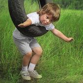Happy boy on swing outdoors — Stock Photo