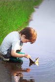 Boy ply in paper ship in puddle — Stock Photo