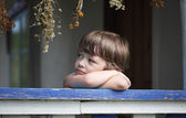 Sad little boy on the porch of rural house — Stock Photo
