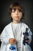 Child with retort and microscope — Stock Photo