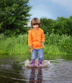 Happy boy jump in puddle — Stock Photo