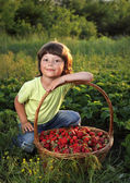 Cheerful boy with a basket of berries — Stock Photo