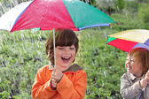 Two happy brother with umbrella outdoors — Stock Photo