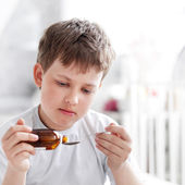 Boy drinking cough syrup — Stock Photo