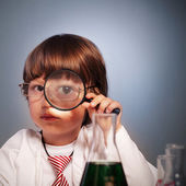 Boy studying a substance in a test tube with a magnifying glass — Stock Photo