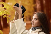 Girl with camera in autumn forest — Stock Photo