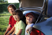 Three cheerful child sitting in the trunk of a car on nature — Stock Photo