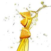 Orange slice in juice stream — Stock Photo