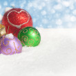 Dreamy image of colorful Christmas ornaments in snow — Stock Photo #8973362
