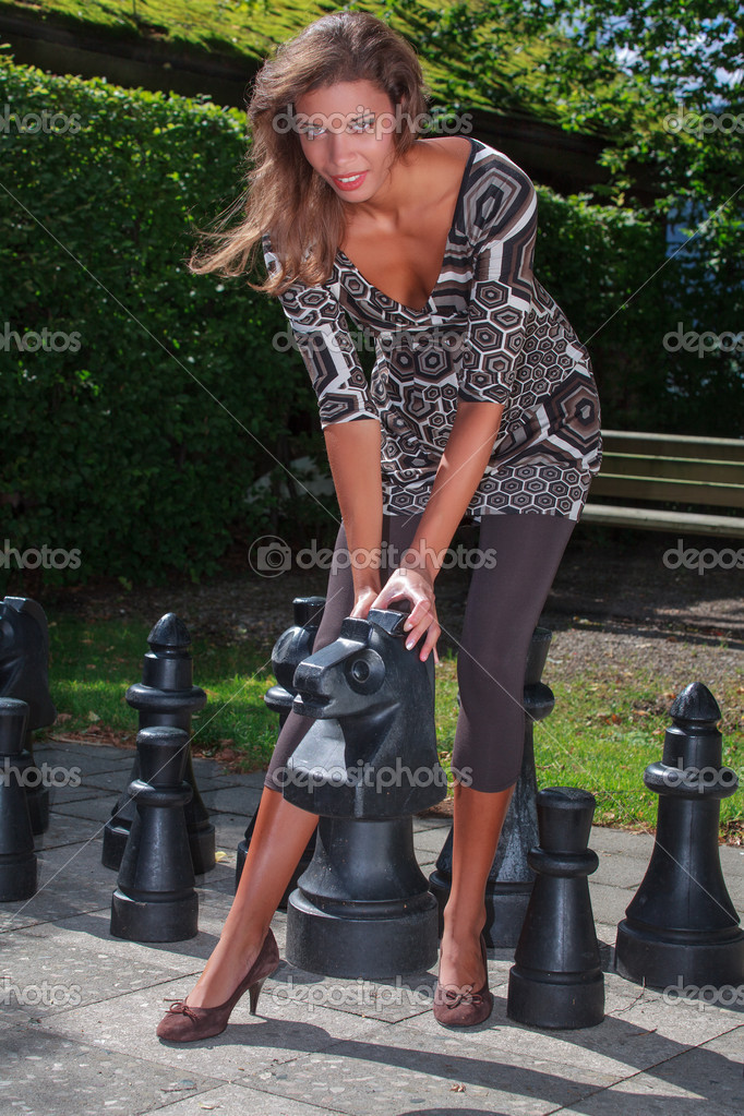 Young woman in stylish outfit playing chess in the park — Stock Photo #12836783