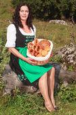 Elderly woman with bread basket — Stock Photo