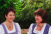 Older women sitting in a Bavarian dirndl together on a bench in the garden — Stock Photo