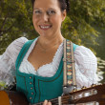 Bavarian woman in dirndl smiling while playing guitar at the lake — Stock Photo