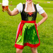 Happy young woman in a dirndl with a beer — Stock Photo