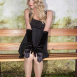 Young woman with long blond hair and elegant mini dress sitting on a bench — Stock Photo