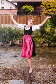 Beautiful girl in a dirndl posing at a stream — Stock Photo