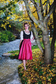 Beautiful woman in a dirndl under an autumn tree — Stock Photo