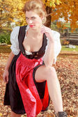 Beautiful woman in a dirndl in an autumn park — Stock Photo