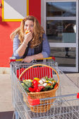 Attractive woman shopping in the food and tasted equally an apple — Stock Photo