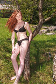 Beautiful redhead teenager in a black bikini — Stock Photo