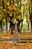 Happy little girl playing with autumn foliage in a park — Photo