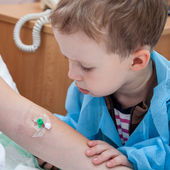 Boy looks at catheter — Foto Stock
