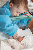 Boy feeding a newborn sister — Stock Photo
