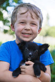 Portrait of boy with puppy — Stock Photo