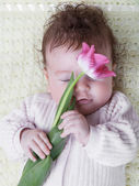 Baby with flowers — Stock Photo