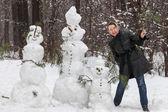 Woman near snowmen — Stock fotografie