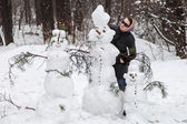 Woman near snowmen — Stockfoto