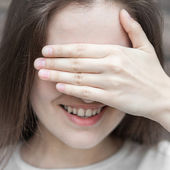 Woman hides her face palm — Stockfoto