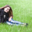 Young woman sits on lawn — Stock Photo