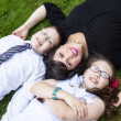 Mother with son and daughter laying in grass — Foto Stock